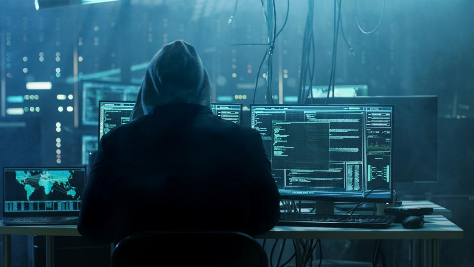 Hooded hacker cyber hacking at a computer screen.