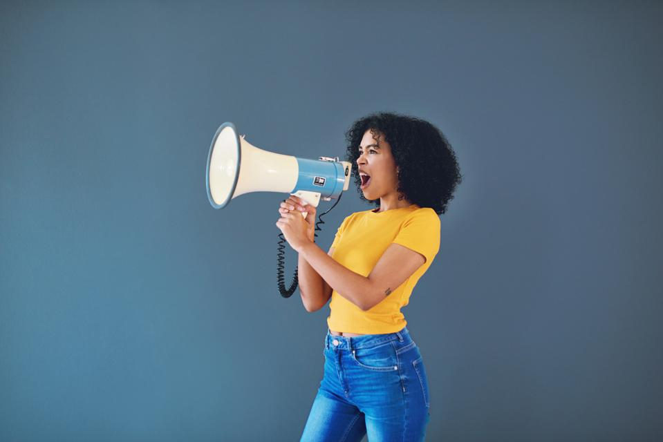 Girl wearing yellow shirt and jeans, holding a megaphone with an open mouth.