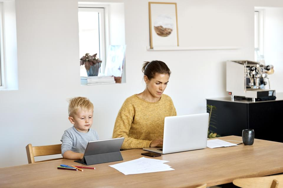 Mother and son using technologies at home