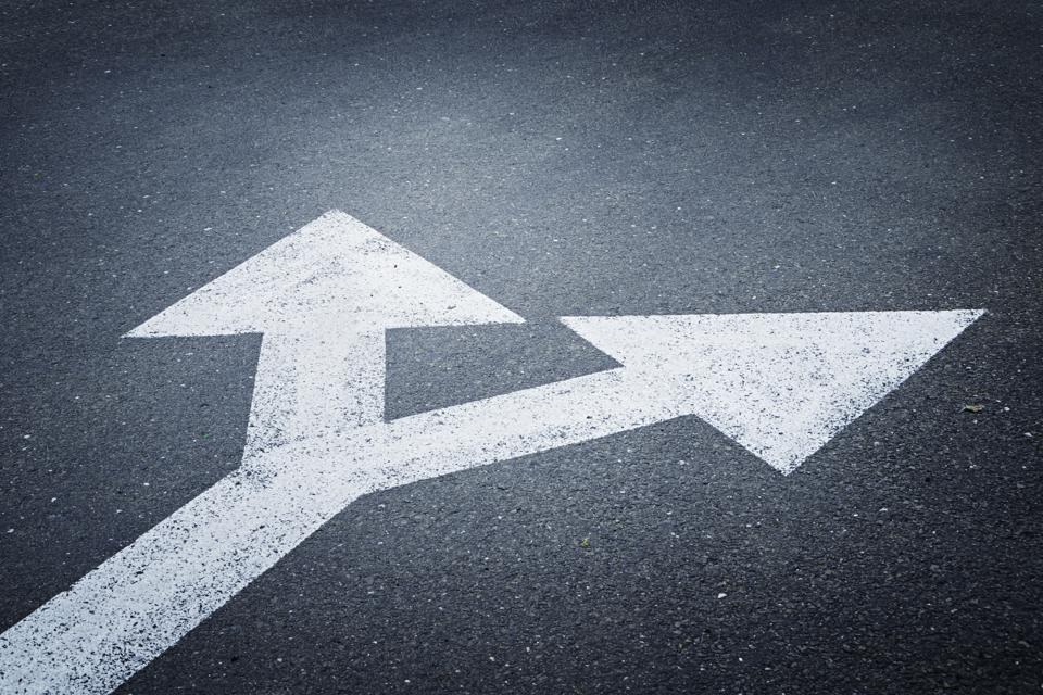 A bi-directional arrow symbol on an asphalt road.
