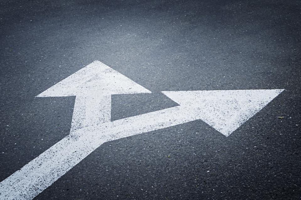 A bi-directional arrow symbol on an asphalt road.