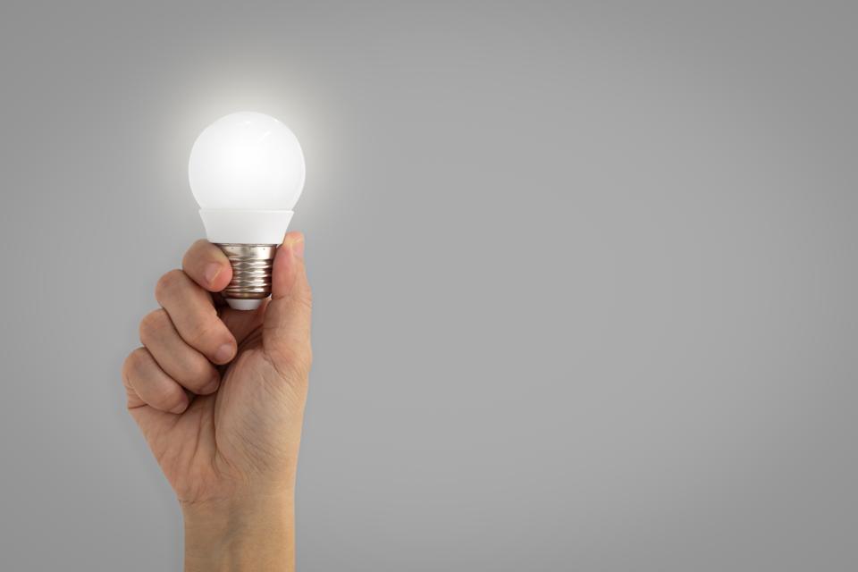 Digital Composite Image Of Hand Holding Illuminated Light Bulb Against White Background