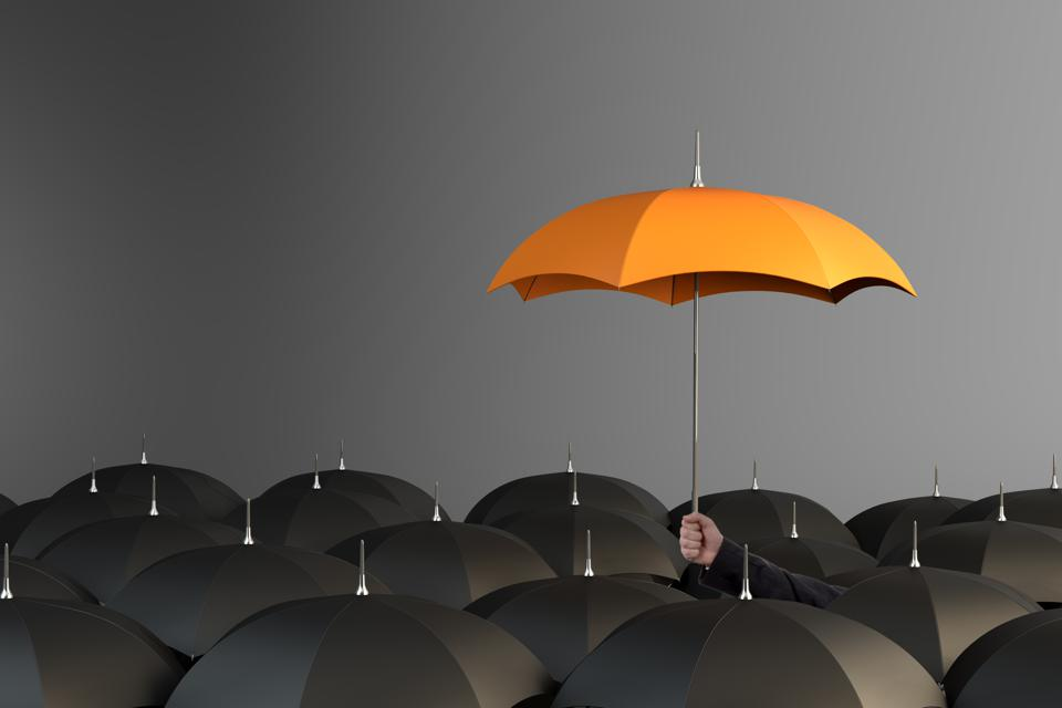 Orange Colored Umbrella Between The Black Umbrellas