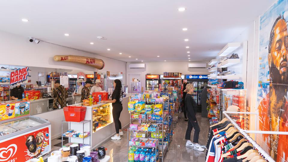 Inside Dank Mart, a bodega in Vancouver. Customers shop in aisles filled with snacks.