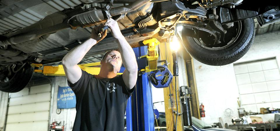 Auto tech Bob Burns installs a new exhaust system on a car at 3 G's Tire & Auto Center in Portland,