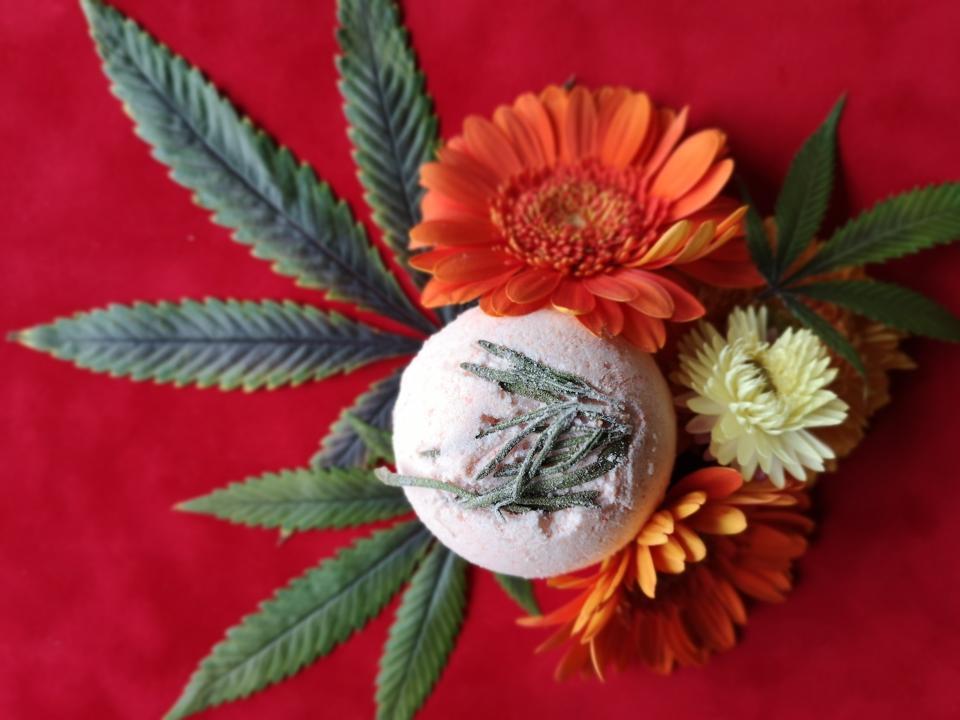 A CBD bath bomb lies on top of a cannabis plant and flowers, made by Arizona-based CBD company Cannabombz.
