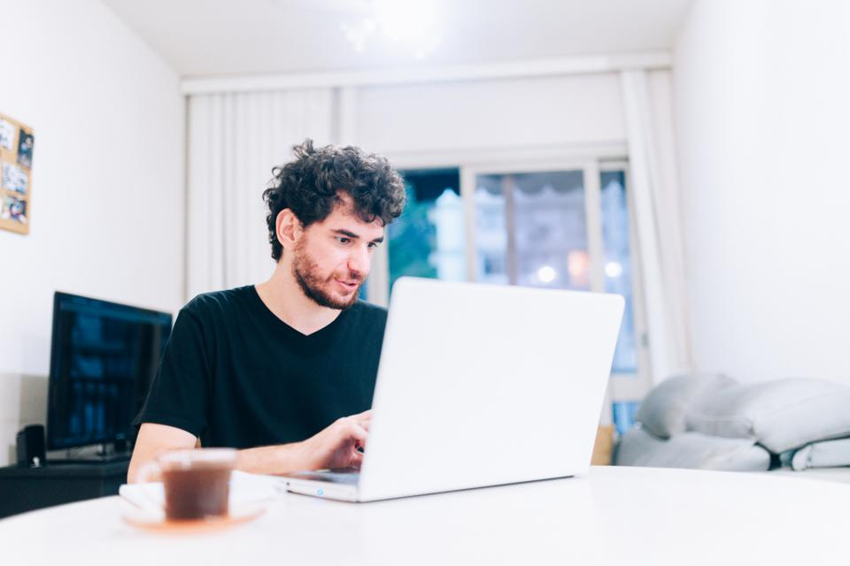 Young man using laptop working at home