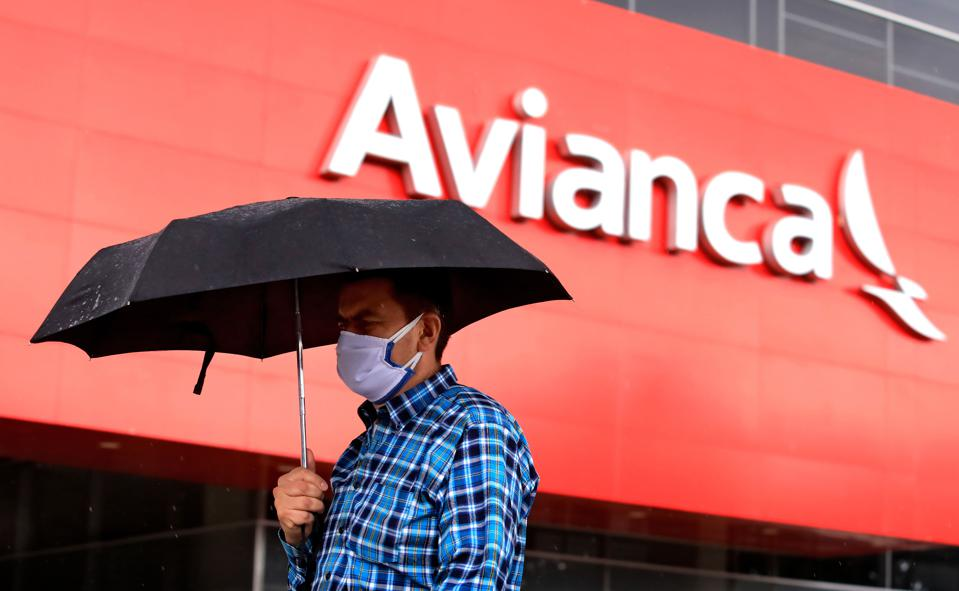 A man wearing a protective face mask and holding an umbrella walks past the Colombian airline Avianca's headquarters in Bogota during the COVID-19 coronavirus pandemic.