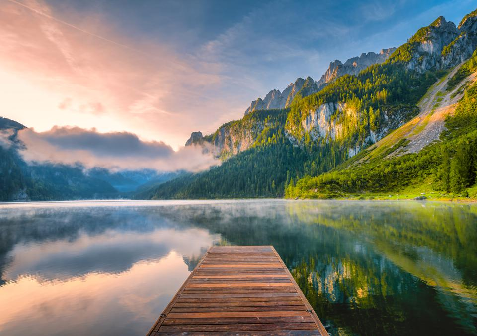 Sunrise Scene of Austrian landscape with forests, fog, meadows, fields and pastures surrounding the lake Gosausee with Alps Mountain