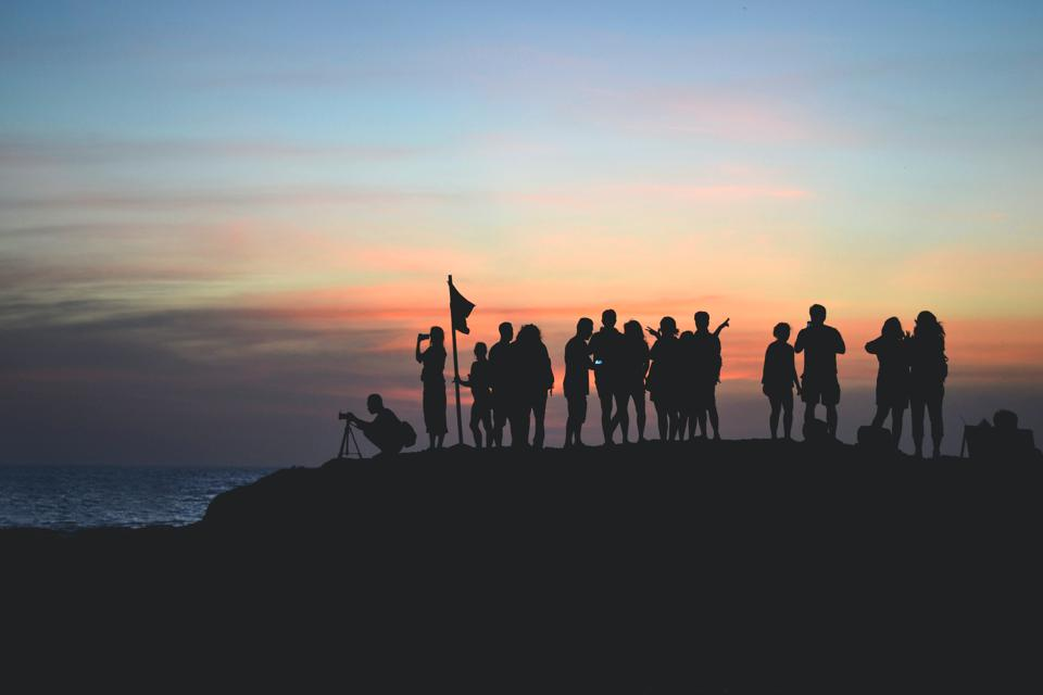 A group of people assembled on seaside cliff at sunset.