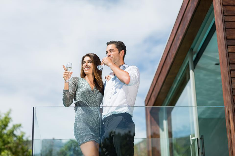 Young couple drinking champagne at balcony