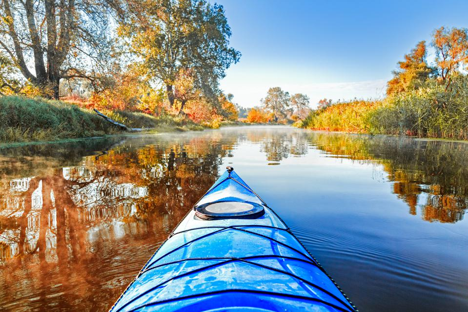 View from kayak in river surrounded by fall trees. Go boating in the fall.