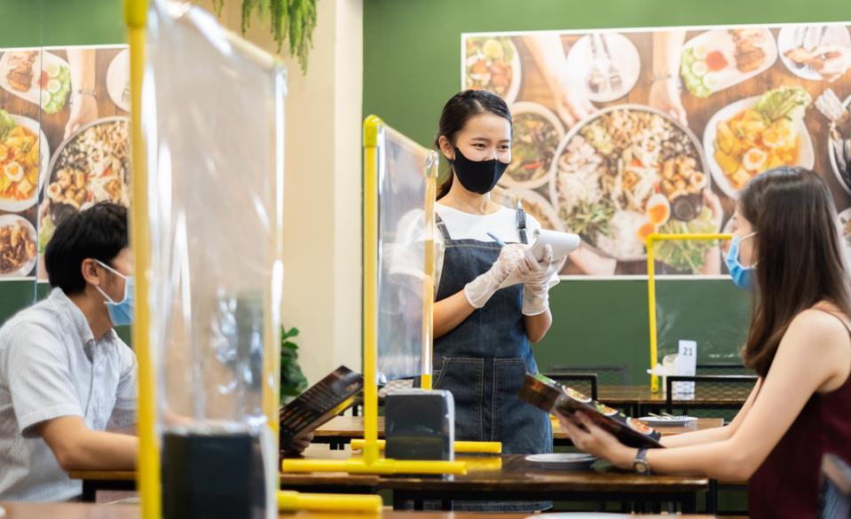 La serveuse de restaurant du personnel asiatique porte un masque protecteur travaillant dans le restaurant avec une distance sociale pour protéger l'infection contre le coronavirus Covid-19