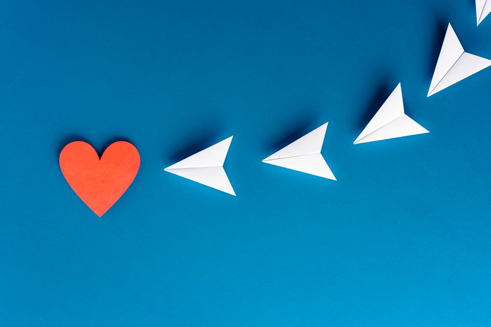 Focus, assertiveness, work yourself concept. Flying paper planes origami with heart shape on blue background. Business and solution concept.