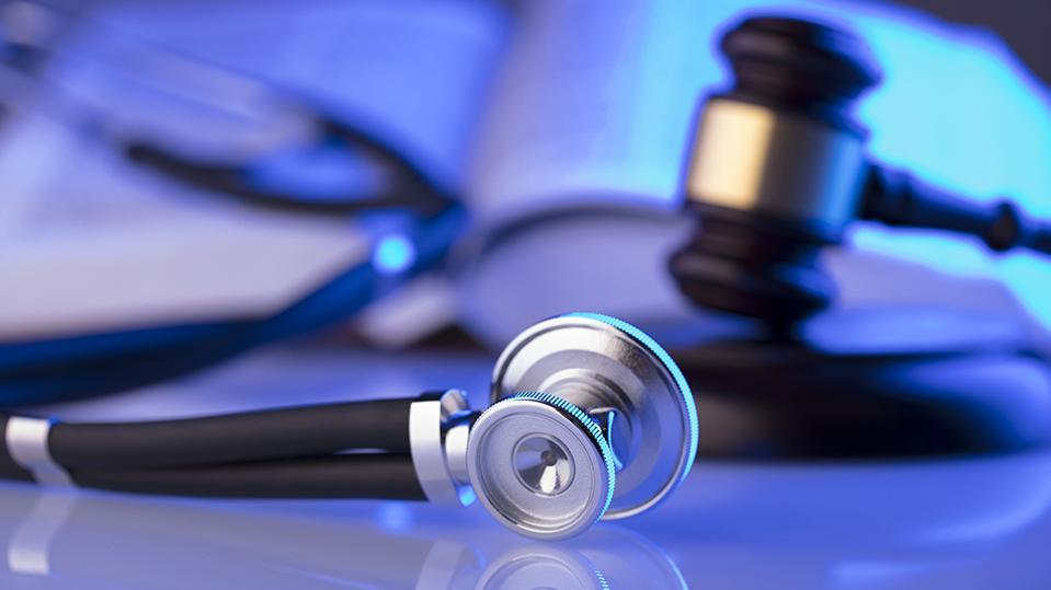 stethoscope sitting next to a gavel