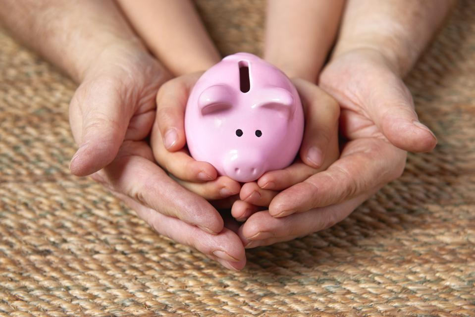 Father and child holding piggy bank