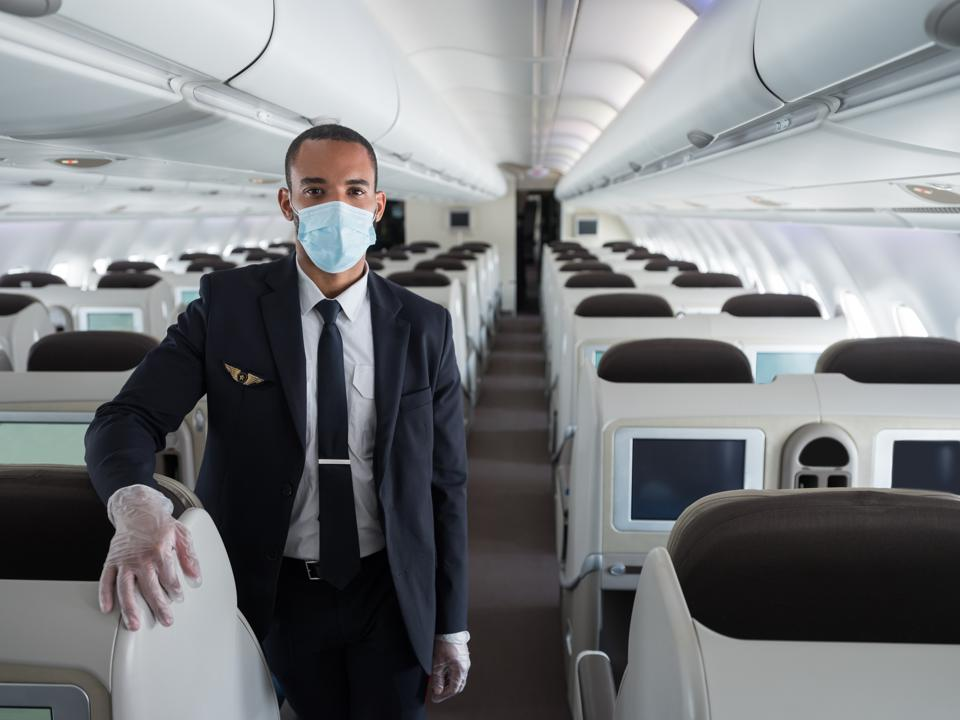 flight attendant on airplane with gloves and mask protection