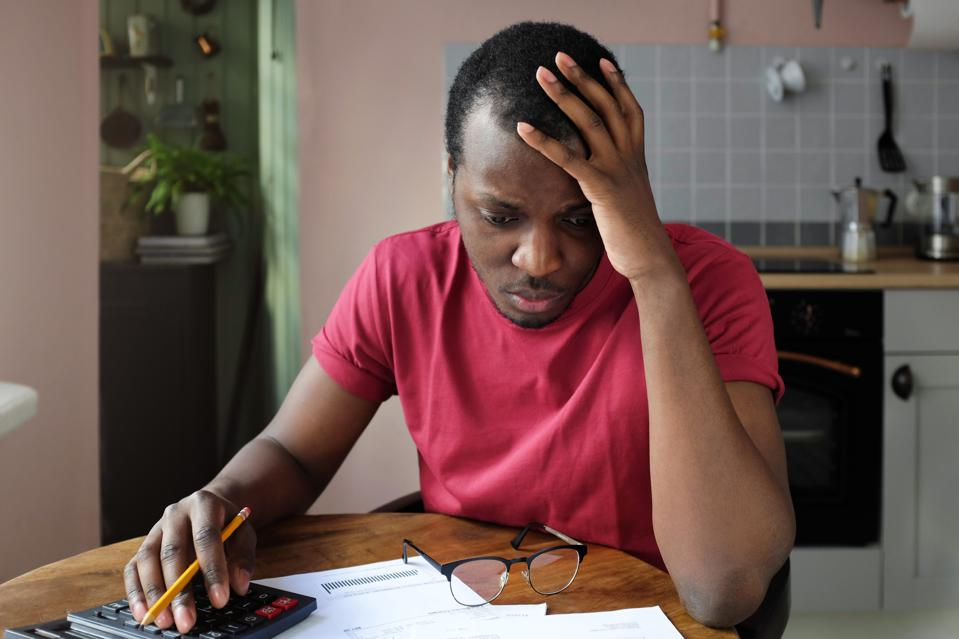 Young  African American man looks desperately at bills, holding head with one hand.