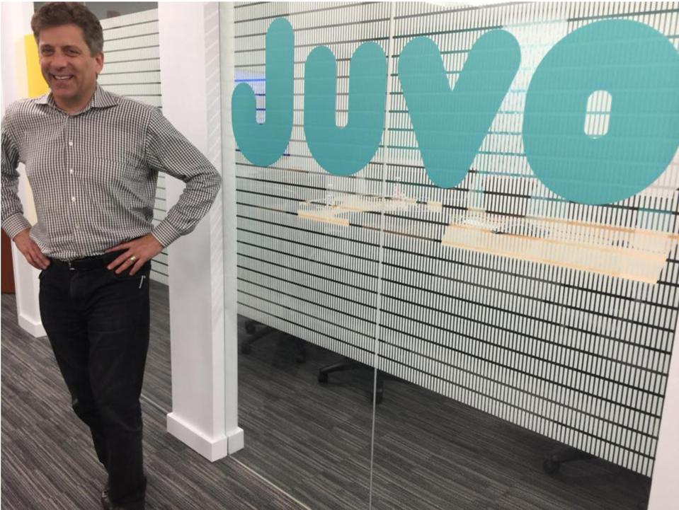 Man standing proudly in office with hands on hips