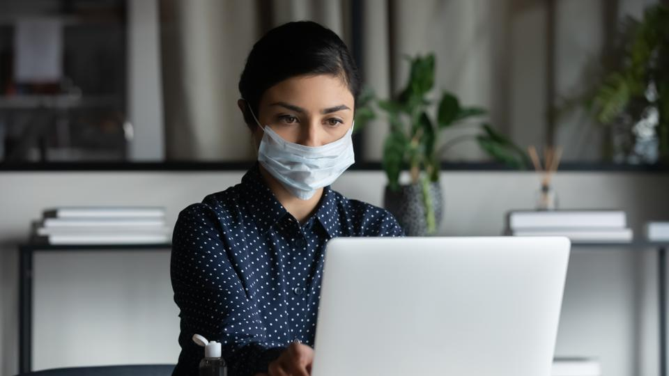 Young female indian professional in facemask working on computer.