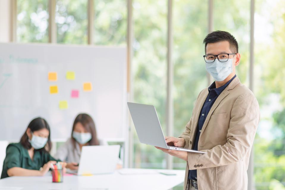 Business employee wearing mask during work in office to keep hygiene follow company policy.