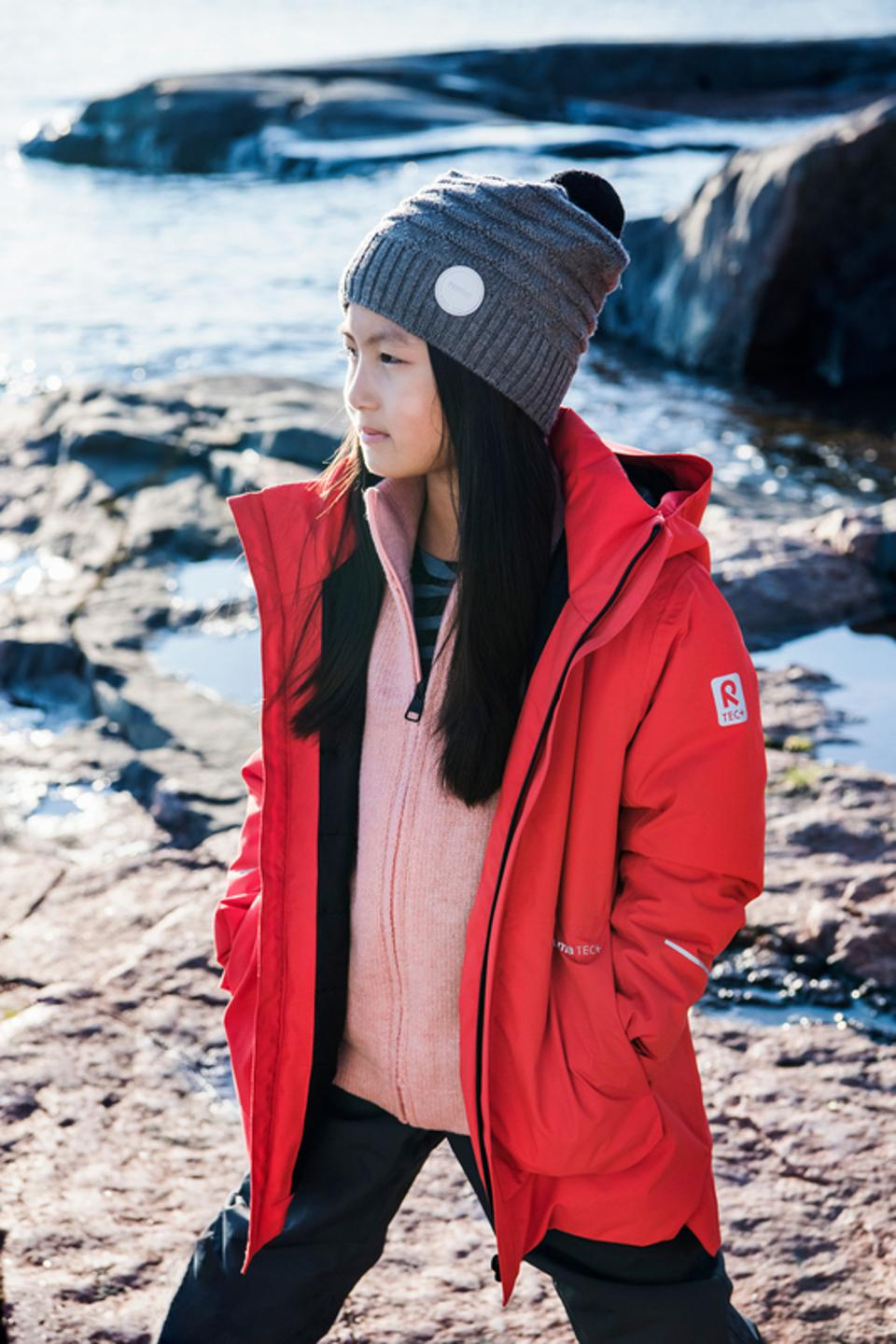 A young girl in the Reima Kulkija winter jacket, which is designed to be 100% recycled.