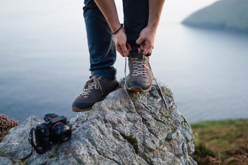 The Bellamont Plus, from Italian footwear brand AKU, being laced up on a rock.