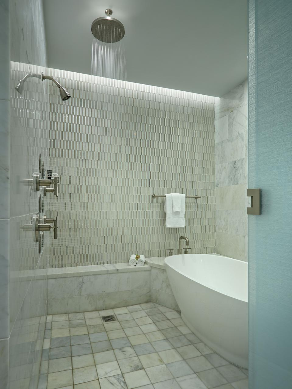 A shower in a hotel that has no door attached to it.