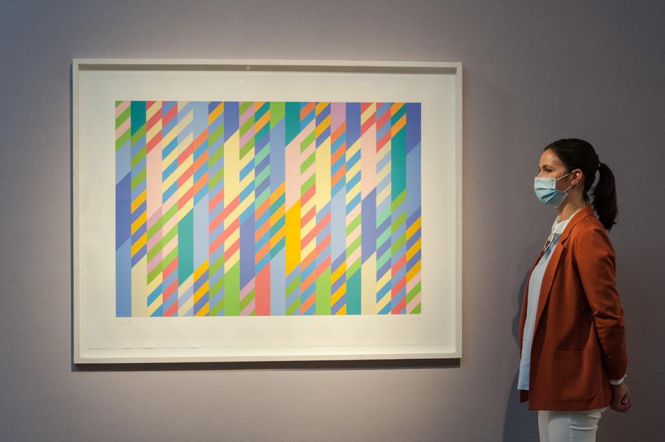 A staff member stands next to 'June', screenprint in colors, 1992-2002, by Bridget Riley (estimated sale price £10,000-15,000) during a press preview at Christie's on September 09, 2020 in London, England.