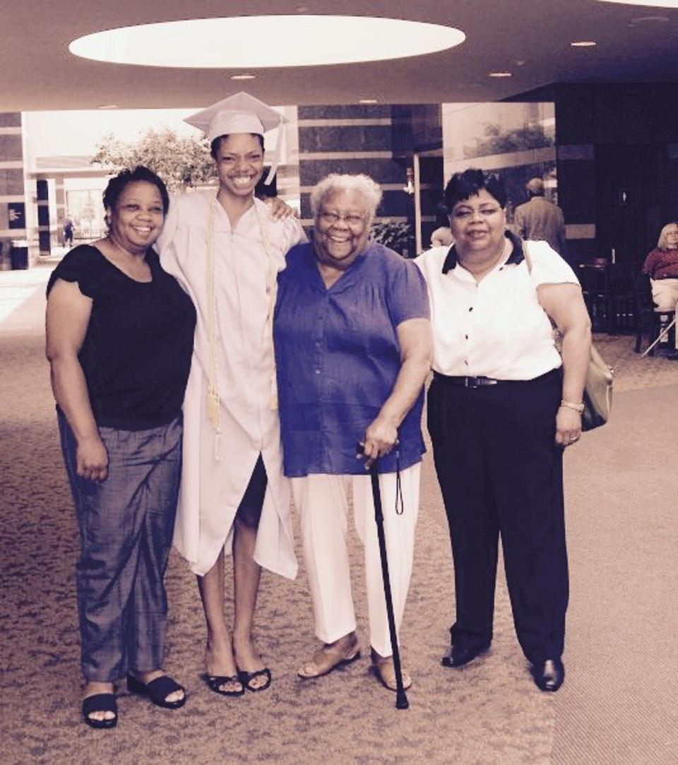 Danielle smiles in her graduation robe, between her aunt, grandmother, and mother.