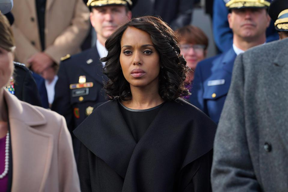 Olivia Pope stands between a crowd of military men, looking sombre, resolved.