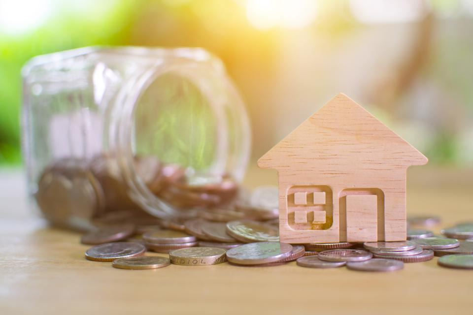 House model and money on light bokeh background.Home loan for new family.Loan for real estate concept.