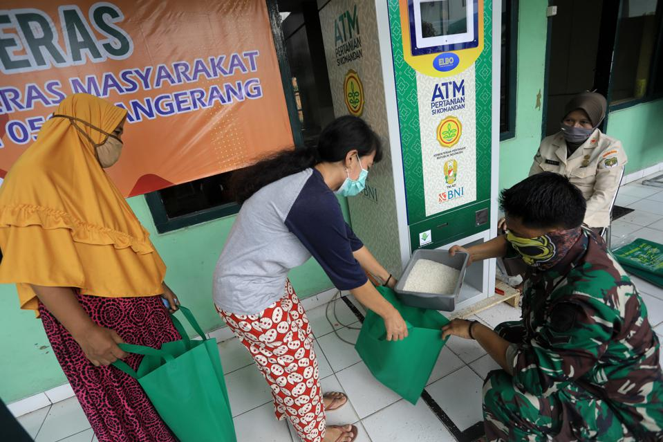 A resident receives free rice at an ATM in Indonesia in 2020