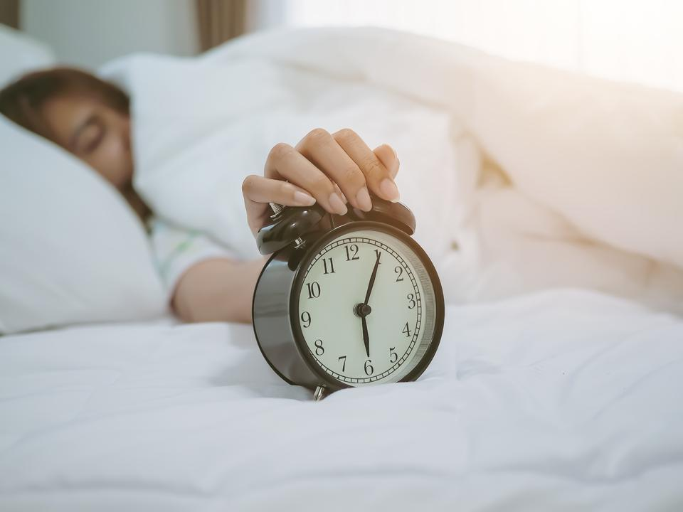 Woman Snoozing Alarm Clock While Sleeping On Bed At Home