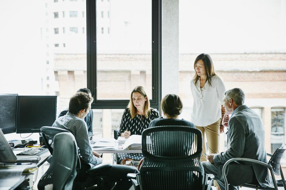 Businesswoman leading planning meeting in office