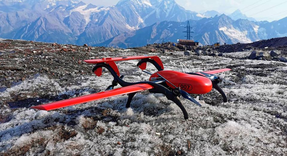 A fixed wing quadcopter sits on top of a mountain.