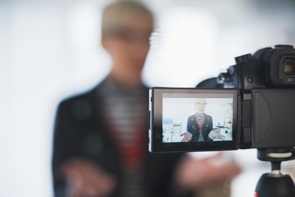Image of mature female vlogger on camera flip screen
