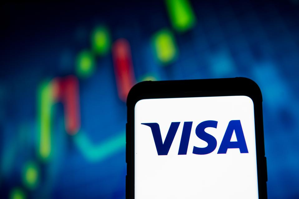 In this photo illustration a VISA logo seen displayed on a...