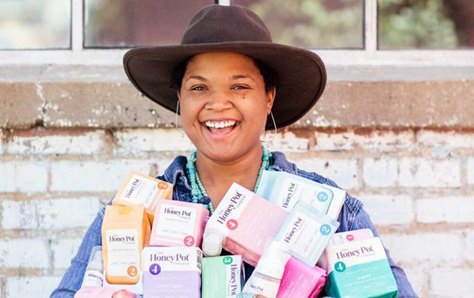 Bea Dixon smiling and holding The Honey Pot products.