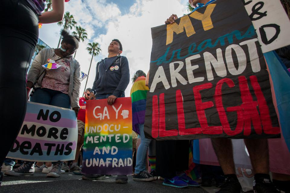 Three people stand at a protest march. They hold signs that say ″My dreams are not illegal,″ ″Gay, undocumented and afraid,″ and ″No more deaths.″ The last two signs are colored to look like the pride and trans flags.