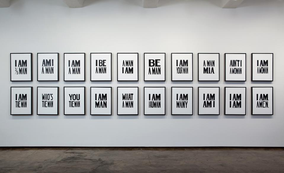 Hank Willis Thomas (American, born 1976), 'I Am. Amen.,' 2009. Liquitex on canvas, 25 1/4 × 19 × 1/4 × 2 1/4 inches each. Installation view. Collection of Ulrich Museum of Art, Wichita State University.