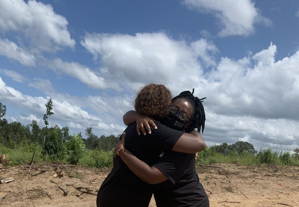 Two women hugging in an open field.