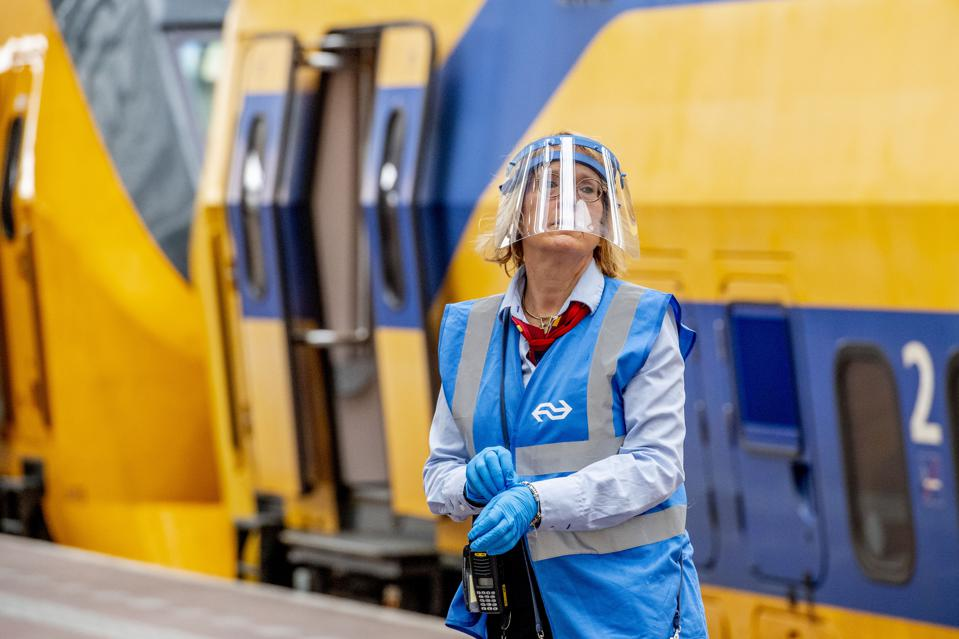 A train station employee wearing a face shield in Rotterdam.