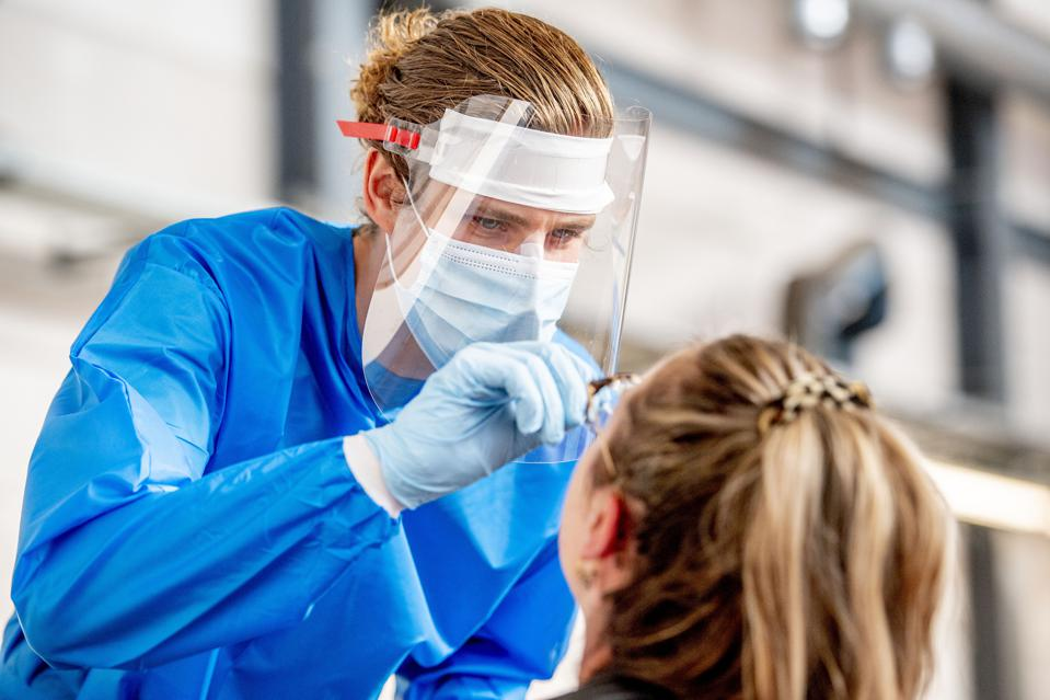 A health worker wearing a face shield collects swab samples...