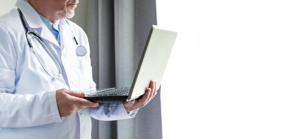 The doctor is advising patients online. Doctor talks to his patient telemedicine during the coronavirus pandemic at his front-to-window from home office. Copy space.