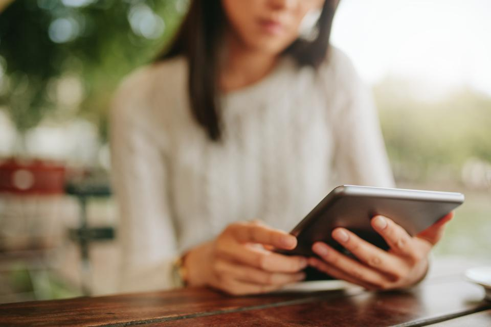 Young female sitting at cafe table with digital tablet