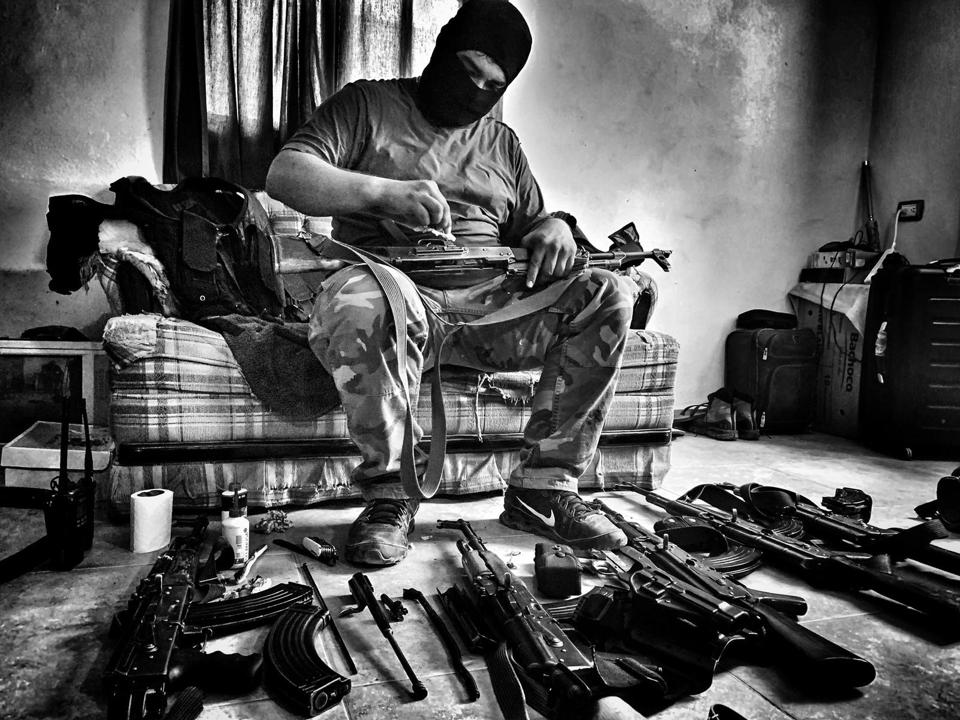 A cartel warrior cleaning his guns.