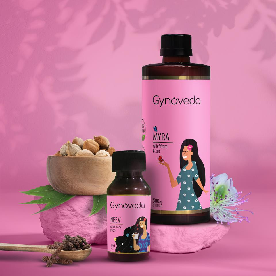 Two pink bottles with the company's name, Gynoveda, on them along other items are on display.
