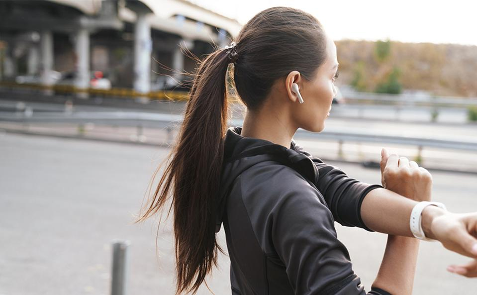 Woman wearing a white pair of Aukey EP-T21 while exercising