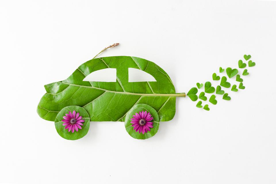 Environmentally friendly car cut out on a green leaf with clovers coming from the exhaust